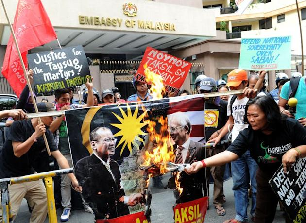 Protesters burn a portrait of Philippine President Benigno Aquino (L) and Malaysian Prime Minister Najib Razak (R) in front of the Malaysian embassy in Manila on March 5, 2013. Malaysian forces searched house-to-house Wednesday after armed Filipino invaders apparently escaped a military assault, as a Philippine guerrilla warned more fighters had arrived
