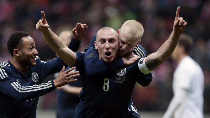 Brown of Scotland celebrates with his teammates scoring a goal against Poland during their international friendly match in Warsaw