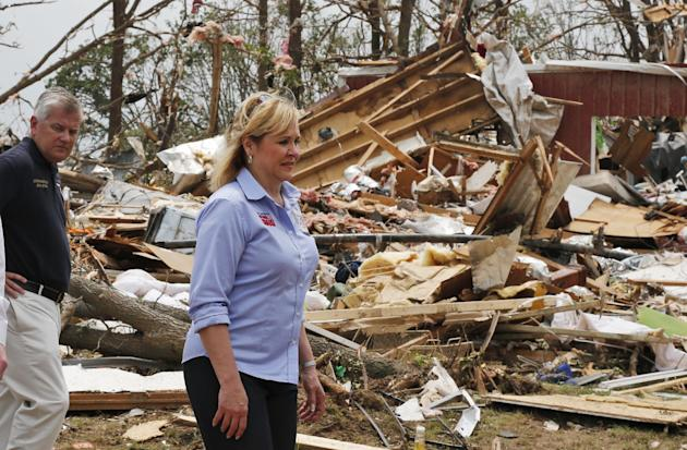 FILE - In this May 20, 2013 file photo, John Doak, left, Oklahoma insurance commissioner, walks with Oklahoma Gov. Mary Fallin, right, through tornado damage near Shawnee, Okla. About 1,000 emergency
