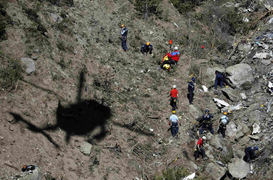 French gendarmes and investigators work amongst the debris of the Airbus A320 at the site of the crash, near Seyne-les-Alpes, French Alps