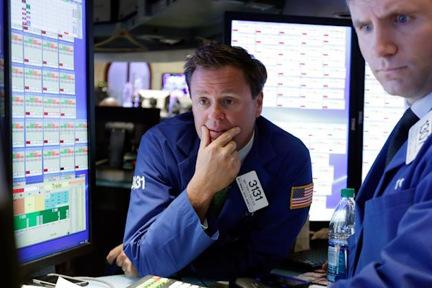 Specialist Matthew Cheslock, left, works on the floor of the New York Stock Exchange, Tuesday, May 26, 2015. Stocks are opening lower on Wall Street as traders return from the Memorial Day holiday in