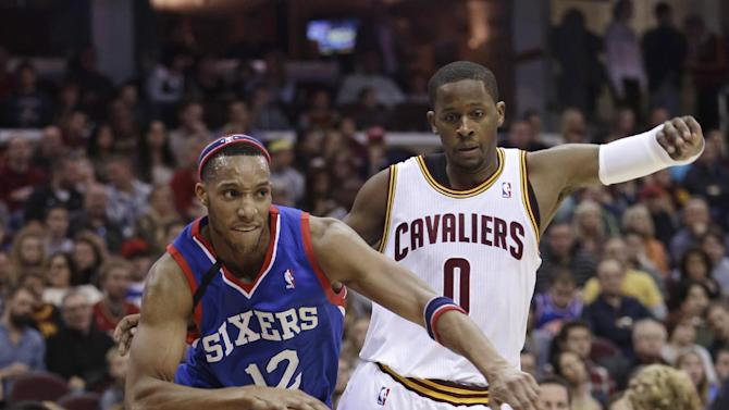 Philadelphia 76ers' Evan Turner (12) drives past Cleveland Cavaliers' C.J. Miles (0) during the first quarter of an NBA basketball game Saturday, Nov. 9, 2013, in Cleveland