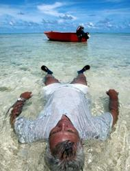 An man relaxes in the waters off Tuvalu as rising sea levels inundate many of his country's low islands. Tiny Pacific nations which are most at threat from rising seas have vowed to dump diesel and other dirty expensive fuels blamed for causing global warming and replace them with clean sources