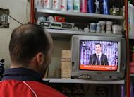 "A man watches Syria's embattled President Bashar al-Assad making a public address on the state-run Syrian TV in Damascus on January 6, 2013. Bashar al-Assad in a rare speech Sunday denounced the opposition as ""slaves"" of the West and called for a national dialogue conference to be followed by a referendum on a national charter and parliamentary elections"