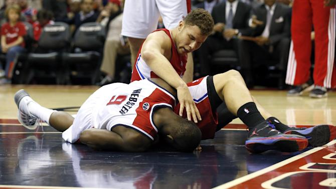 Los Angeles Clippers forward Jared Dudley (9) checks on Washington Wizards forward Martell Webster (9) after Dudley stepped on him after his dunk, in the first half of an NBA basketball game, Saturday, Dec. 14, 2013, in Washington. Webster continued to play