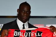 Mario Balotelli poses with his AC Milan jersey at San Siro Stadium on Friday after his transfer from Manchester City. Balotelli's departure for AC Milan this week will mean fewer off-the-pitch headlines for Manchester City players but some analysts think his exit leaves manager Roberto Mancini with inadequate strike options