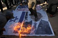 Palestinian Salafists walk on a picture of US President Barack Obama while burning Israeli and US flags during a protest against an amateur film mocking Islam in Rafah in the southern Gaza Strip, September 14. Furious protesters targeted symbols of US influence in cities across the Muslim world on Friday, attacking embassies, schools and restaurants in retaliation for a film that mocks Islam