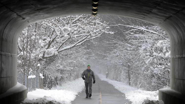 A man approaches a tunnel as he walks under a canopy of snow covered trees on the Monon Trail in Carmel, Ind., Monday, March 25, 2013. More than seven inches of snow fell in Central Indiana. (AP Photo/Michael Conroy)