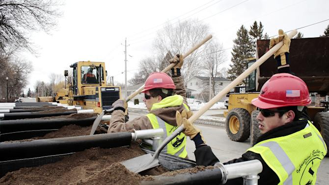 Jeremiah Poitra, right, and Chase Nygaard work to fill TrapBags on Monday April 22, 2013, along fifth street south as part of the city's flood preparation efforts in Fargo, N.D.  (AP Photo/The Forum, Michael Vosburg)