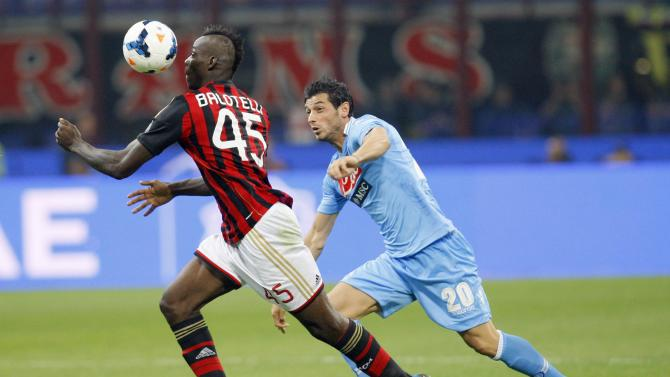 AC Milan's Balotelli challenges Dzemaili of Napoli during their Italian Serie A soccer match at the San Siro stadium in Milan