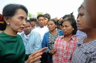 Myanmar pro-democracy icon Aung San Suu Kyi (L) speaks with villagers in Monywa northern Myanmar on March 14, 2013. Suu Kyi will visit Japan from April 13 through 19, according to a Japanese statement