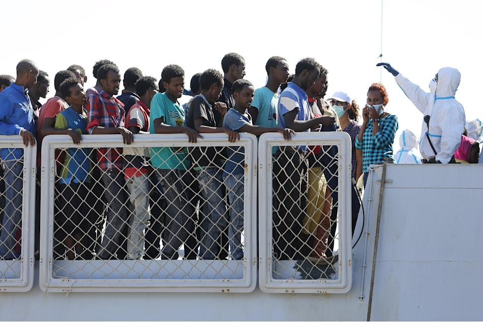 Migrants wait to disembark from an Italian navy vessel in the Sicilian harbour of Augusta