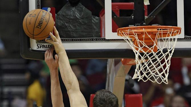 Golden State Warriors' Andrew Bogut (12) blocks the shot of Houston Rockets' Chandler Parsons, left, during the first quarter of an NBA basketball game Friday, Dec. 6, 2013, in Houston
