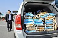 A South Korean walks past a car packed with bags of rice at the inter-Korean transit office in Paju on April 17, 2013. Ten representatives of the 123 South Korean firms in Kaesong had applied for permission to visit the zone, two weeks after the North blocked all access. About 200 South Koreans have stayed in Kaesong to keep their companies running