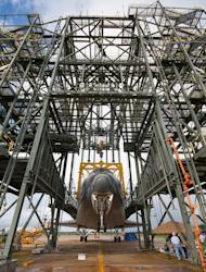 The nose landing gear of space shuttle Endeavour is lifted during operations to raise the shuttle for securing to the Shuttle Carrier Aircraft (SCA) on Sept. 14, 2012. The shuttle is inside the Mate-Demate Device at the Shuttle Landing Facility