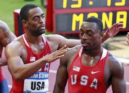 Gay of U.S hugs teammate Gatlin after competing in 4 x 400 m men's event at the Herculis Athletics Meet at Louis II stadium in Monaco