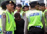 "An Indonesian woman walks past Indonesian policemen in Jakarta on February 20, 2012. An Indonesian woman drowned her nine-year-old son in the bath, claiming she was worried that his ""small penis"" would affect his prospects for the future, a police spokesman said Thursday"