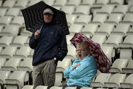 Spectators with umbrellas wait as rain falls during the third one-day international between England and Australia at Edgbaston cricket ground in Birmingham September 11, 2013. REUTERS/Philip Brown