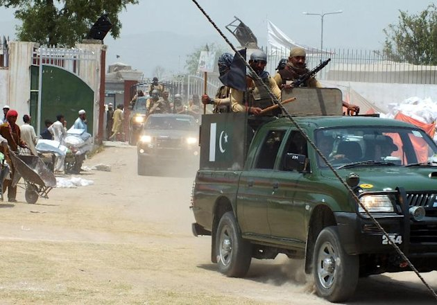 Pakistani troops patrol at a relief distribution point for civilians ...