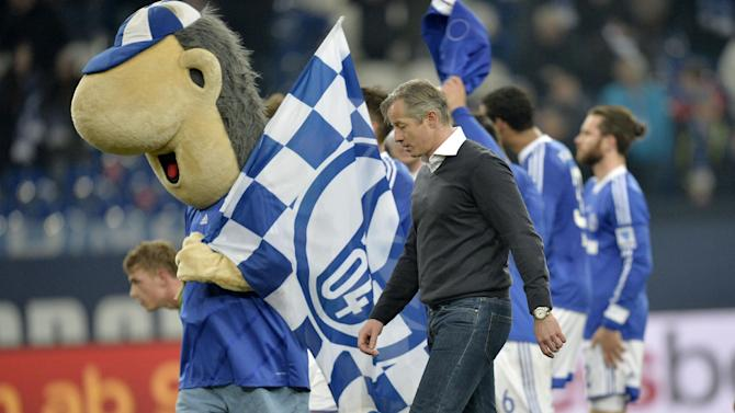 Schalke head coach Jens Keller walks behind the mascot after the German Bundesliga soccer match between FC Schalke 04 and VfL Wolfsburg in Gelsenkirchen,  Germany, Saturday, Feb. 1, 2014