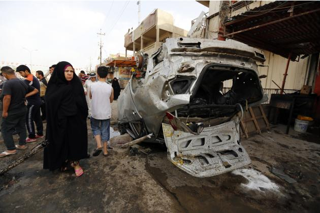 Woman walks past the site of a car bomb attack in Baghdad's Habibiya district