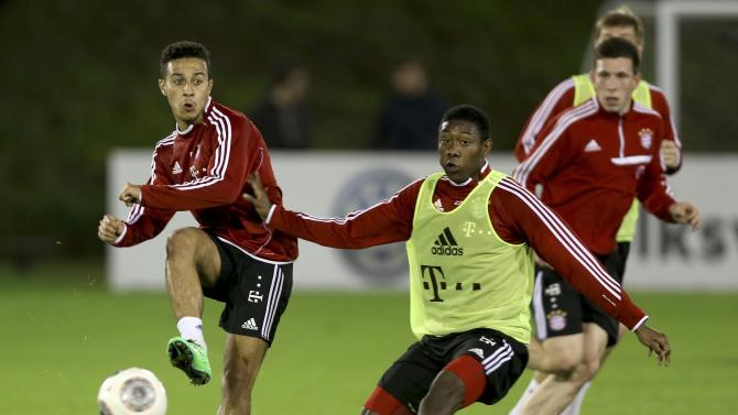 Bayern Munich's David Alaba (R) fights for the ball with Thiago Alcantara during a training session at the Aspire Academy for Sports Excellence in Doha