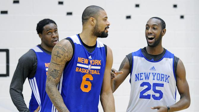 New York Knicks' C.J. Leslie (25) reacts after competing in a shooting drill with Tyson Chandler (6) as Ike Diogu looks on at the teams NBA basketball training camp Tuesday, Oct. 1, 2013, in Greenburgh, N.Y