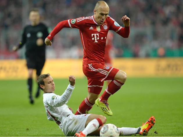 Bayern Munich's Arjen Robben overcomes a challenge from Kaiserslautern's Chris Loewe (L) during the match in Munich on April 16, 2014