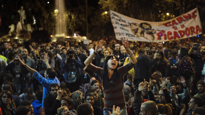 "Protestors shout during a demonstration near the Spanish Parliament against austerity measures announced by the Spanish government in Madrid, Spain, Wednesday, Sept. 26, 2012. Spain's Parliament has taken on the appearance of a heavily guarded fortress with dozens of police blocking access from every possible angle ahead of a protest against the conservative government's handling of the economic crisis. Banner reads ""Meat for the grinder."" (AP Photo/Daniel Ochoa De Olza)"
