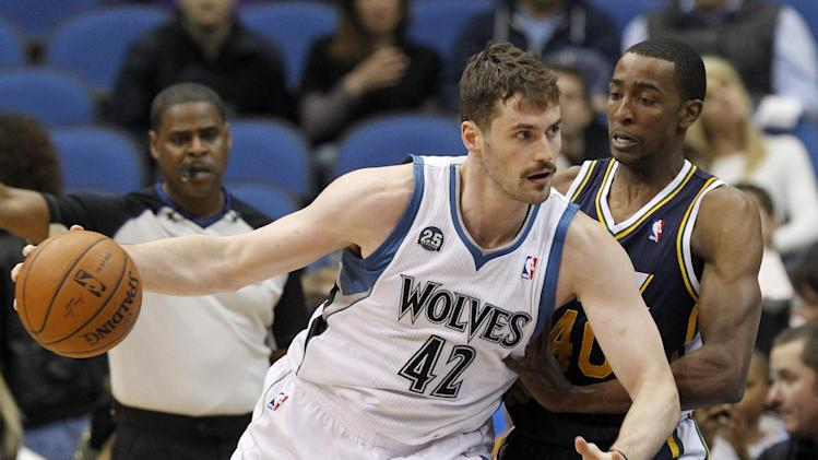 Minnesota Timberwolves forward Kevin Love (42) drives against Utah Jazz forward Jeremy Evans, right, during the first quarter of an NBA basketball game in Minneapolis, Wednesday, April 16, 2014