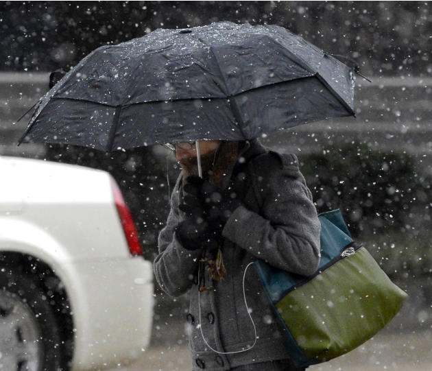 A woman walks during a brief snow shower in downtown Birmingham, Ala., Thursday, Feb. 6, 2014. A rare winter storm paralyzed the Birmingham area last week. (AP Photo/ AL.com, Mark Almond)