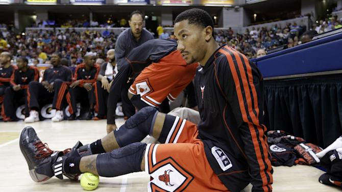 Chicago Bulls guard Derrick Rose uses a softball to loosen up a muscle as he sits in front of the bench in the first half of an NBA preseason basketball game against the Indiana Pacers in Indianapolis, Saturday, Oct. 5, 2013