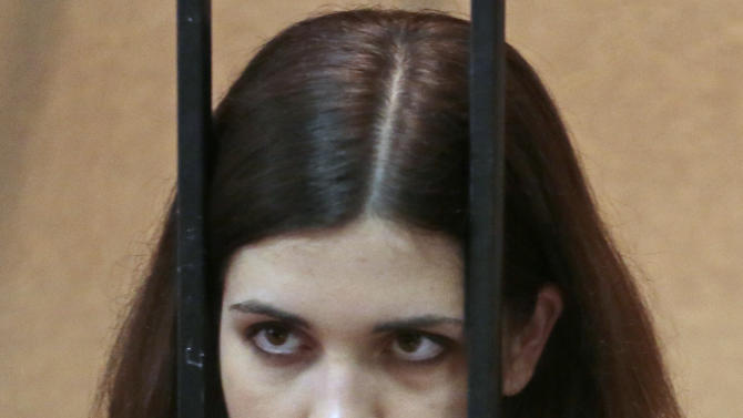 Nadezhda Tolokonnikova, a member of the feminist punk band, Pussy Riot, listens from behind bars at a district court in Zubova Polyana 440 km Southeast of Moscow in Russia's province of Mordovia, Friday, April 26, 2013. A Russian court is to consider whether one of the jailed Pussy Riot members is eligible for early release. Nadezhda Tolokonnikova, in custody since her arrest in March 2012, is serving a two-year sentence for the band's irreverent protest against President Vladimir Putin in Moscow's main cathedral. (AP Photo/Mikhail Metzel)
