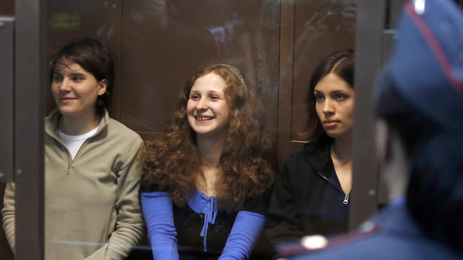 CORRECTS LEFT TO RIGHT  Feminist punk group Pussy Riot members, from left, Yekaterina Samutsevich,  Maria Alekhina,  and Nadezhda Tolokonnikova sit in a glass cage at a court room in Moscow, Wednesday. Oct. 10, 2012. Three members of the punk band Pussy Riot are set to make their case before a Russian appeals court that they should not be imprisoned for their irreverent protest against President Vladimir Putin. Their impromptu performance inside Moscow's main cathedral in February came shortly before Putin was elected to a third term. The three women were convicted in August of hooliganism motivated by religious hatred and sentenced to two years in prison. (AP Photo/Sergey Ponomarev)