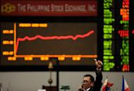 A Filipino trader gestures in front of the electronic display at the Philippine Stock Exchange (PSE) in Manila on June 18. Standard & Poor's raised the Philippines' long-term foreign currency credit rating to within one rung of investment grade on Wednesday, citing the government's improving finances