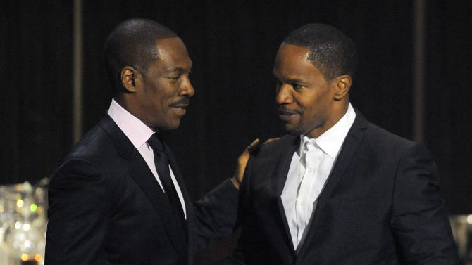 "Eddie Murphy, left, is greeted onstage by actor/comedian Jamie Foxx at ""Eddie Murphy: One Night Only,"" a celebration of Murphy's career at the Saban Theater on Saturday, Nov. 3, 2012, in Beverly Hills, Calif. Murphy and Foxx were cast members in the 2006 film ""Dreamgirls."" (Photo by Chris Pizzello/Invision)"