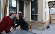 File - In this March 13, 2014 file photo, Dave Mullins, right, kisses his husband Charlie Craig, on the patio of their home in Westminster, Colo. The couple filed a legal complaint with the Colorado Civil Rights Commission against Denver-area baker Jack Phillips, who refused to make a wedding cake for the two men, citing his religious beliefs. Colorado's Civil Rights Commission on Friday upheld a judge's ruling that Phillips cannot refuse to make wedding cakes for same-sex couples, saying that doing so violates state laws prohibiting businesses from discriminating against gay people. (AP Photo/Brennan Linsley, file)