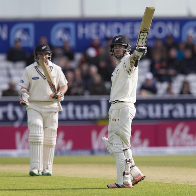 As his teammate Tom Latham looks on New Zealand's Luke Ronchi raises his bat as he reaches 50 on the first day of the second Test match between England and New Zealand at Headingley cricket ground