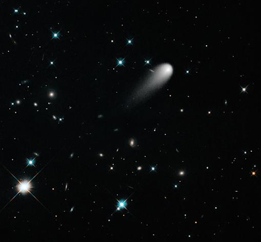 The sun-approaching Comet ISON floats against a seemingly infinite backdrop of numerous galaxies and a handful of foreground stars in this Hubble Space Telescope composite image, taken in April 2013.