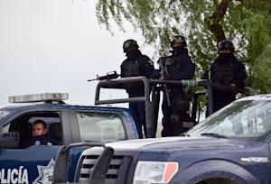 Mexican Federal Police vehicles and officers armed…