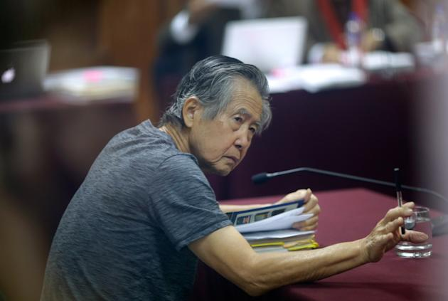 Jailed former President Alberto Fujimori, photographed through a glass window, attends his trial at a police base on the outskirts of Lima, Peru, Wednesday, April 23, 2014. Fujimori, who is already se