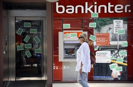 A woman walks past the entrance of a Bankinter bank branch which was plastered with stickers from the Mortgage Victims Platform (PAH) in Mataro
