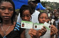 People hold their ID cards as they wait in line to vote on November 17 in Freetown. Sierra Leone political parties urged calm on Sunday as the nation braced for results after a peaceful day of voting in polls seen as a litmus test of the west African nation's post-war recovery