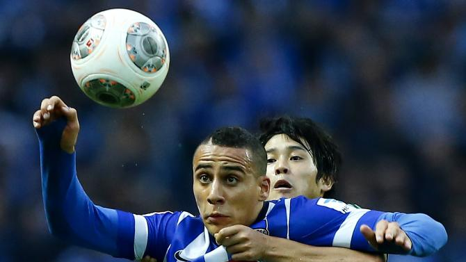 Hertha Berlin's Ben-Hatira and Schalke 04's Atsuto head for ball during German first division Bundesliga soccer match in Berlin