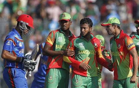 Afghanistan's Tarakai leaves field as Bangladesh's Al Hasan and teammates celebrate dismissal during ICC Twenty20 World Cup match in Dhaka