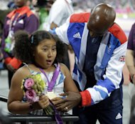 Great Britain's Mohamed Farah shows off his gold medal to his stepdaughter Rihnna after the awards ceremony for the men's 5000-meter during the athletics in the Olympic Stadium at the 2012 Summer Olympics, London, Saturday, Aug. 11, 2012. (AP Photo/Matt Slocum)