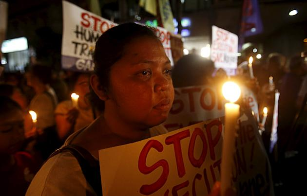 Activists display placards as they hold a candlelight vigil for death row prisoner Mary Jane Veloso outside Indonesian embassy in Makati