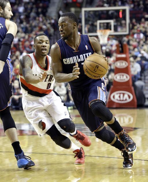 Charlotte Bobcats guard Kemba Walker, right, drives past Portland Trails Blazers guard Damian Lillard during the first half of an NBA basketball game in Portland, Ore., Thursday, Jan. 2, 2014