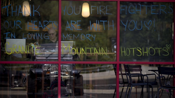 A message written on the window of a local coffee shop, Wednesday, July 3, 2013, in Prescott, Ariz., is addressed to the 19 Granite Mountain Hotshot firefighters who died when an out-of-control blaze overtook them near Yarnell, Ariz. on Sunday. From the picturesque town square to famous Whiskey Row, life goes on in Prescott, but so, too, does the mourning for their lost heroes, some of them native sons. (AP Photo/Julie Jacobson)