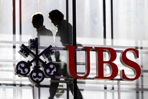Employees walk past a logo of the Swiss banking giant UBS on October 30, 2012 in Zurich. The bank has been slapped with $1.5 billion in fines for manipulating global interest rates, also tampered with Swiss franc interest rates for more than a decade, a Swiss newspaper reported Sunday.